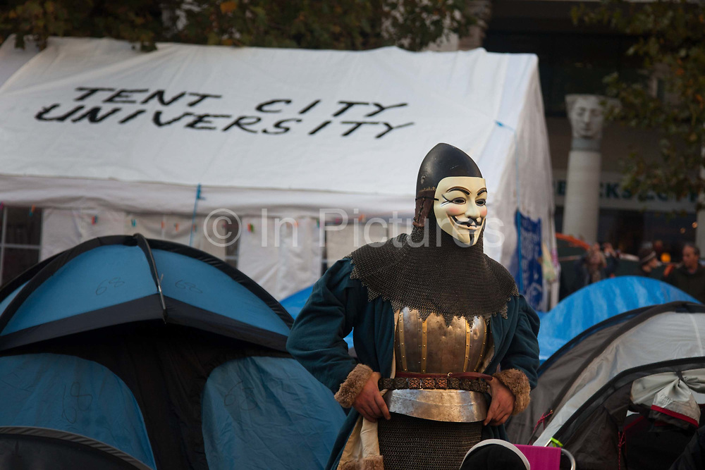 An activist dressed as a knight wearing an Anonymous face mask stands in the middle of Tent City, the Occupy London's Stock Exchange' s camp outside St Paul's Cathedral.