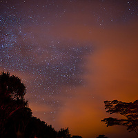 Clouds lit by the lights of Pahoa drift under the milky way.