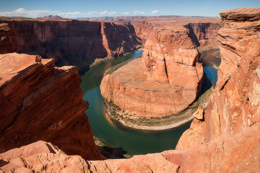 An Emerald Ring<br /> Horse Shoe Bend, Colorado River, AZ.<br /> Water is married to the landscape of the Southwest.  Smaller streams may dry up, flash floods self-expend, but the Colorado is eternal.  It is the desert's lover.    Perhaps this is where the river made a proposal, and placed a ring, however imperfect, around the mesa opposite me.  Standing on the rim, there is a sense of the depth of love that preserved that finger.  The jade complements my sun burned arena, it is nature's color wheel.  I, too, got an emerald ring, and put it on an elegant finger, for the sake of love. It wasn't the first ring…although I have never given one lightly.  Because within it, destinies have collided.  Within it, loyalty and faith should need no definition.  But the ring I gave must not have been perfect, somehow the braid was broken.  The bond of that ring must have poured out of the gap in the continuum.  Or maybe justifications poured in, corrupting the concept of it, and of all the rings before.  It was my fault, to believe the idea was stronger than the circle.  In the end it is the wearer's choice to honor, or not, and I think the desert has more forever in it than we sad human beings do.  People think this is a vast wasteland—I can only say my feelings differ.  I can admire the comfort of the relationship I see out there, and realize my solitary is within.