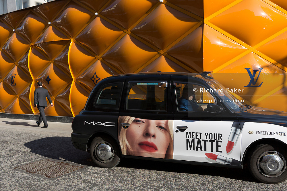 A black cab with advertising for a lipstick brand on the door drives past the temporary renovation hoarding of luxury brand Louis Vuitton in New Bond Street, on 27th February 2019, in London, England.