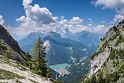 From a hike to Lake Coldai using a lift high on Monte Civetta, look down to Alleghe resort village and its turquoise lake in the Dolomites, Belluno province, Veneto region, Italy, Europe. On the horizon, see Marmolada (center, highest peak in the Dolomites) and the Sella Group (right). Alleghe Lake was formed in 1771 by a landslide from adjacent Mount Piz. The Dolomites or Dolomiti are part of the Southern Limestone Alps in Europe. UNESCO honored the Dolomites as a natural World Heritage Site in 2009.