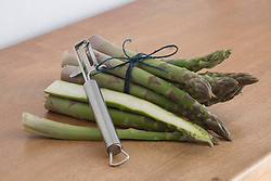 Bunch of green asparagus with peeler on the table