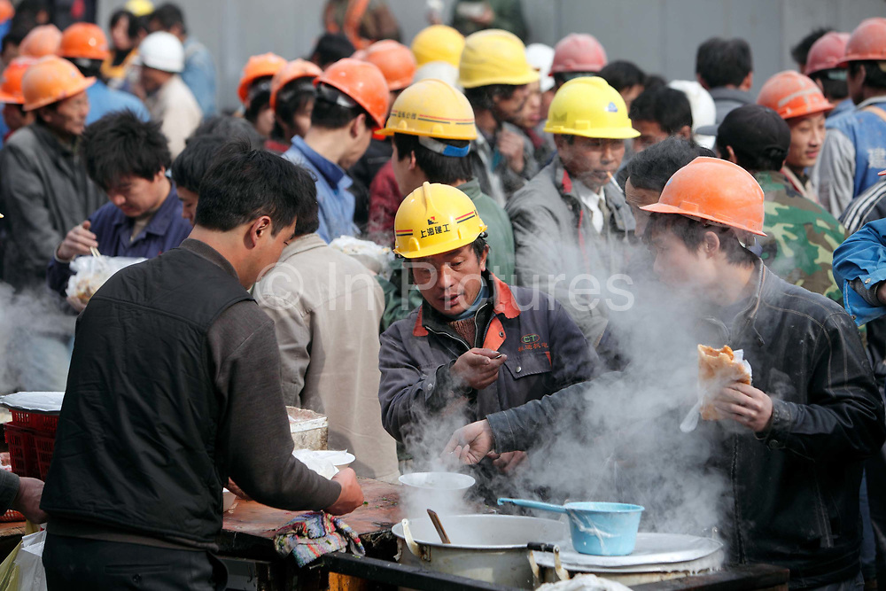 Workers gather for lunch at a makeshift eating area near a construction site in the Lujiazui Financial District of Shanghai, China on 29 December, 2009.  While China owes much of its recent economic revival to the vast and cheap labor force made up by hundreds of millions of migrant workers, it is facing an uncertain future as the number of able bodied workers have passed their peak and wage continues to rise.