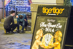 © Licensed to London News Pictures . 01/01/2015 . Manchester , UK . A man , ejected from Tiger Tiger, is consoled by another as he sits on steps with his head in his hands . He is missing special guest Danny Dyer . Revellers usher in the New Year on a night out in Manchester City Centre .  Photo credit : Joel Goodman/LNP