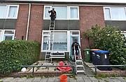 Nederland, Deest, 22-9-2018 Een glazenwasser, glazenwassers, lapt de ramen van een woonhuis. Foto: Flip Franssen