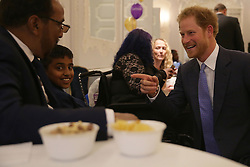 Prince Harry (right) reacts as he meets Most Caring Child Award Winner Armaan Aslam (second left) and his father Mohammad (left), as he attends the WellChild Awards in London. The awards recognise the courage of seriously ill children, their families and carers.