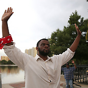 """DeQuan Shanks leads protesters in raising their arms at Lake Eola park during the """"National Moment of Silence"""" event at the Lake Eola bandshell in downtown Orlando, Florida on Thursday, August 14, 2014. In light of the recent killing of eighteen year old Mike Brown in Ferguson, Missouri, citizens across America are gathering in solidarity to hold vigils and observe a moment of silence to honor victims of suspected police brutality. (AP Photo/Alex Menendez)"""