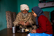 Young Punjabi girl, Jasbir Kaur, being feed breakfast by her grandfather at home, Chita Kallan village, Punjab, India