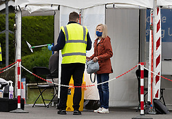 © Licensed to London News Pictures. 19/06/2021. Tattenham Corner, UK. A local resident hands over a completed PCR covid-19 test at a mobile test centre at Tattenham Corner, Surrey. Surge testing for the coronavirus is taking place in parts of Surrey after a rise in infections caused by the delta variant. Photo credit: Peter Macdiarmid/LNP