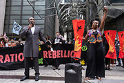 Impassioned speaker talks of the history of Lloyd's of London outside their offices on the Walk of Shame disruptive mach through the City of London by environmental group Extinction Rebellion on 4th September 2020 in London, United Kingdom. The walk visited various locations in the financial district, to protest against companies and institutions with historical links to the slave trade, or who finance or insure projects which are seen as ecologically unsound. The message by the group is that 'apologies and token attempts at diversity are not enough to address this legacy and present reality. Our demand is reparations and reparatory justice for those affected by colonial and neo-colonial exploitation'. Extinction Rebellion is a climate change group started in 2018 and has gained a huge following of people committed to peaceful protests. These protests are highlighting that the government is not doing enough to avoid catastrophic climate change and to demand the government take radical action to save the planet.