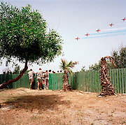 Spectators at the The Princess Margaret Hospital (TPMH) on the Akrotiri peninsula, about 4 kilometres from the RAF Station at Akrotiri, admire the elite 'Red Arrows', Britain's prestigious Royal Air Force aerobatic team, as they perform one of their first public shows of the year. RAF staff and patients are allowed on to the grass outside the hospital building for this free show, given in honour of local charity fund-raisers of the Cyprus-based RAF Association whose guests form one of the smallest crowds to watch a Red Arrows display. Here, the team perform The Twizzle manoeuvre in front of the small crowd who stand by a green fence, matching tree and palm tree stumps. The bare earth is baked hard by the lack of rain and it almost looks like a desert scene as five of the nine jets speed overhead.