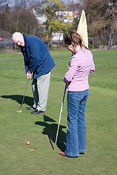 Older man and his carer playing pitch and put,