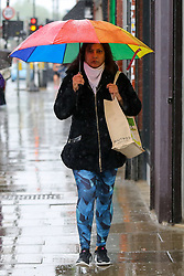 © Licensed to London News Pictures. 04/06/2021. London, UK. A woman shelters from the rain beneath a LGBTQ+ coloured umbrella during rainfall in north London. According to The Met Office, more rain is expected today across London and the South East of England, with the hot weather returning tomorrow. Photo credit: Dinendra Haria/LNP