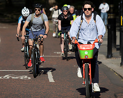 © Licensed to London News Pictures. 02/06/2021. London, UK. Members pf the public cycle during sunny weather in Westminster in Central London. Temperatures are expected to rise with highs of 28 degrees forecasted for parts of London and South East England today . Photo credit: George Cracknell Wright/LNP