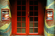 Tabu night club entrance in Vienna, Austria. Red painted french doors with dirty window panes from top to bottom and a camoflaged paint job for the exterior walls. Two small marquees on either side of door with red trim and illustrated posters.