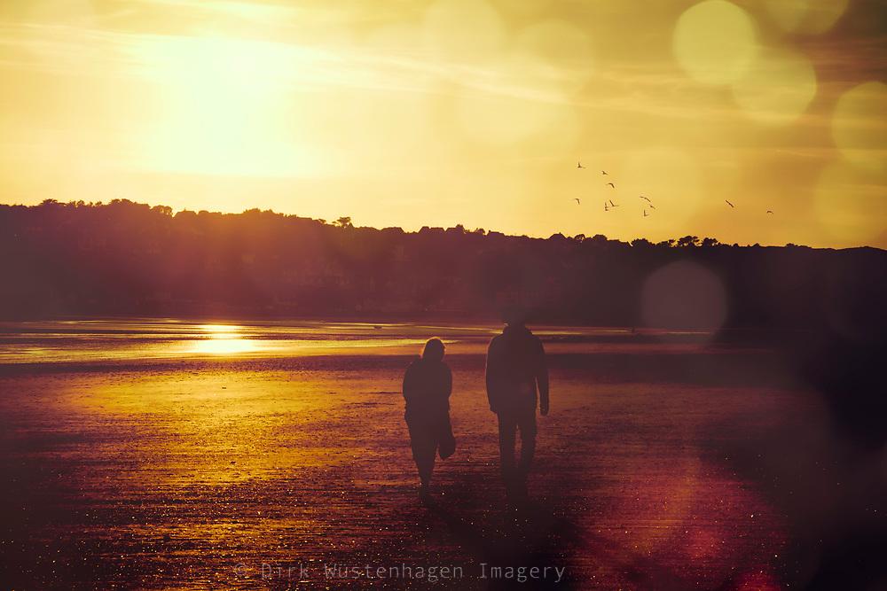A couple enjoying a beach walk at sunset