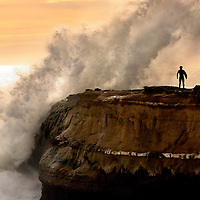 A surfer pauses before entering the lineup as a wave crashes at the tip of Lighthouse Point in Santa Cruz, California.<br /> Photo by Shmuel Thaler <br /> shmuel_thaler@yahoo.com www.shmuelthaler.com