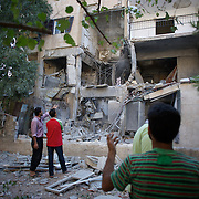 August 10, 2012 - Aleppo, Syria: Local people access the damage of their residential building cause by Syrian Army bombardments in Haneno neighborhood in central Aleppo...The Syrian Army have in the past week increased their attacks on residential neighborhoods where Free Syria Army rebel fights have their positions in Syria's commercial capital, Aleppo. (Paulo Nunes dos Santos/Polaris)