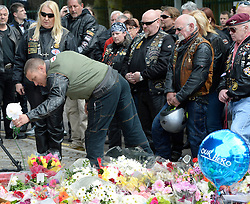 © London News Pictures. 25/05/2013. Woolwich, UK. Over A group of bikers pay their respects, one lays a white flower. 200 bikers ride to  Woolwich Barracks in South East London to pay tribute to Drummer Lee Rigby and lay flowers.  Drummer Lee Rigby was murdered by two men in Woolwich town centre in what is being described as a terrorist attack. Photo credit: Ben Cawthra/LNP