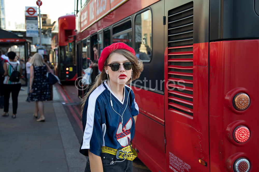 Young woman wearing a beret with matching bright red lips on London Bridge in London, England, United Kingdom.