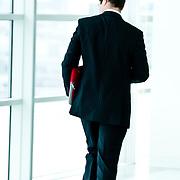 Rear view of business man walking in office