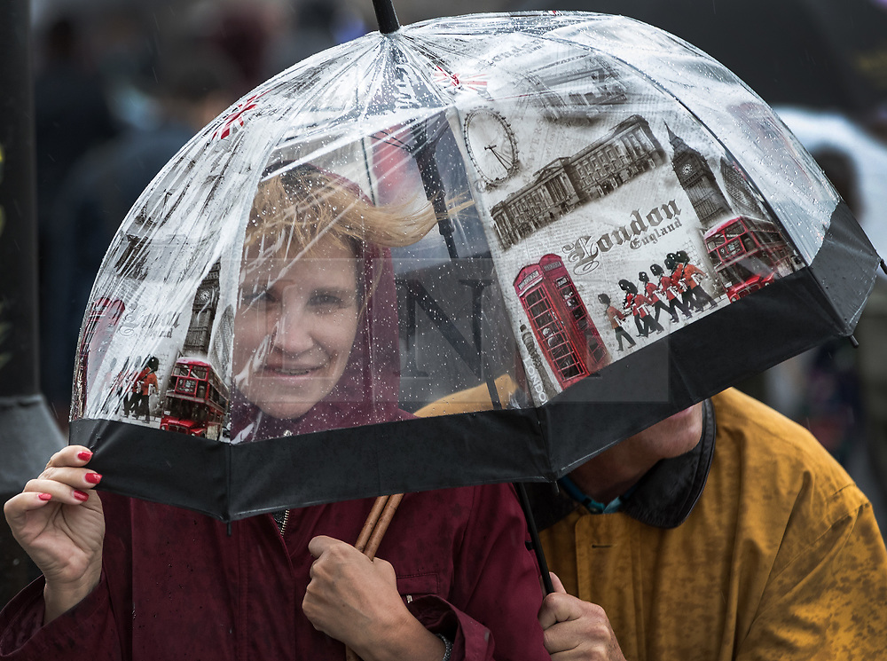 © Licensed to London News Pictures. 18/08/2017. London, UK. Tourists near Parliament shelter under a London themed umbrella as a sudden burst of heavy rain hits central London. Today's weather has been a mixture of sunshine and showers for most of the UK. Photo credit: Peter Macdiarmid/LNP