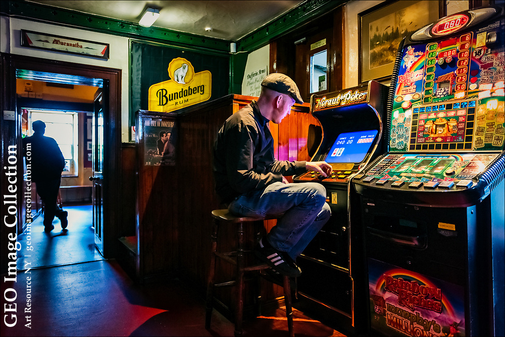In the solitude of the tiny Dufferin Arms pub in Killyleagh, a patron plays a gaming machine. London's Financial Times newspaper reports that the blinking lights of game machines are fading as more pubs move upmarket in food and decor, others close, and patrons turn to other games with larger jackpots.