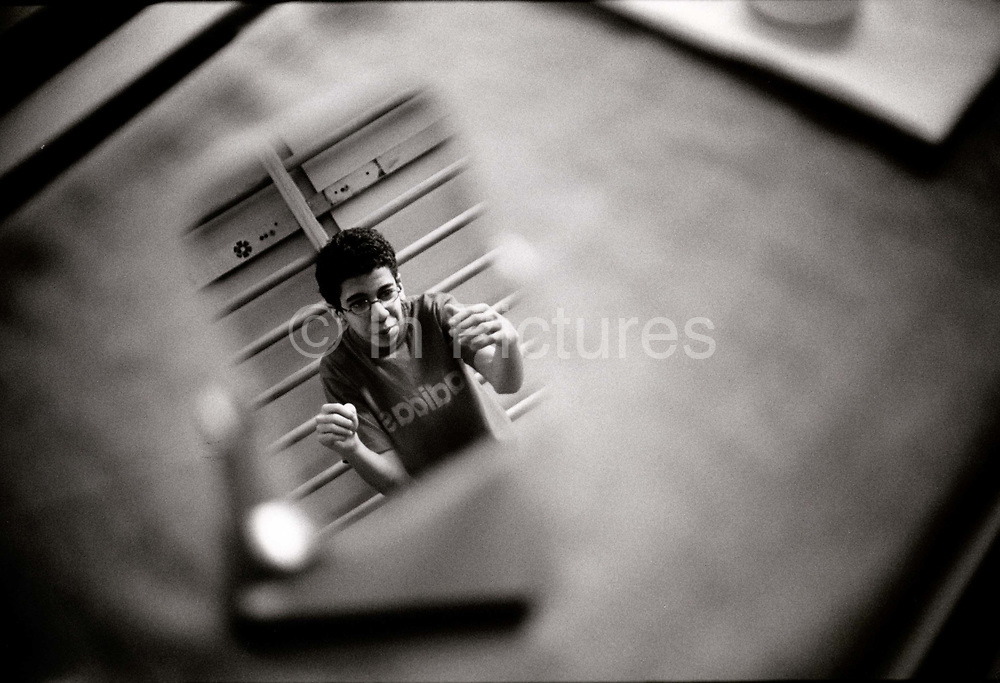 Sherif, 14, is reflected in a mirror while making his walking exercises