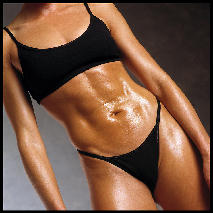 Tan oiled up woman bodybuilder in exercise attire. cropped from  shoulders to thighs and flexing abdomen..