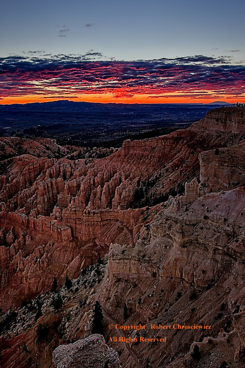 Bryce Sunset: The breathtaking view of a sunset from Bryce Point as it cast the last light of the day over a veritable sea of hoodoos in Bryce National Park, Utah, United States of America.<br /> <br /> In amongst the hoodoo's one can find a trail winding through a rocky archway.