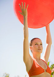 Portrait of young beautiful woman holding red swiss ball arms stretched