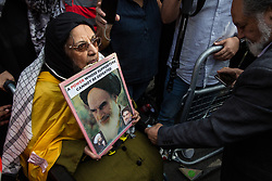 London, UK. 10th June, 2018. A woman in a wheelchair carrying an image of Ayatollah Khomeini arrives to take part in the pro-Palestinian Al Quds Day march through central London organised by the Islamic Human Rights Commission. Pro-Israel activists tried to block her passage. An international event, Al Quds Day began in Iran in 1979.