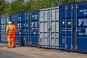 Two men dressed in orange high-visibility work clothes stand next to a row of blue metal storage shipping containers in a self-storage depot on 17th June 2019 in Aldershot, Hampshire, United Kingdom.