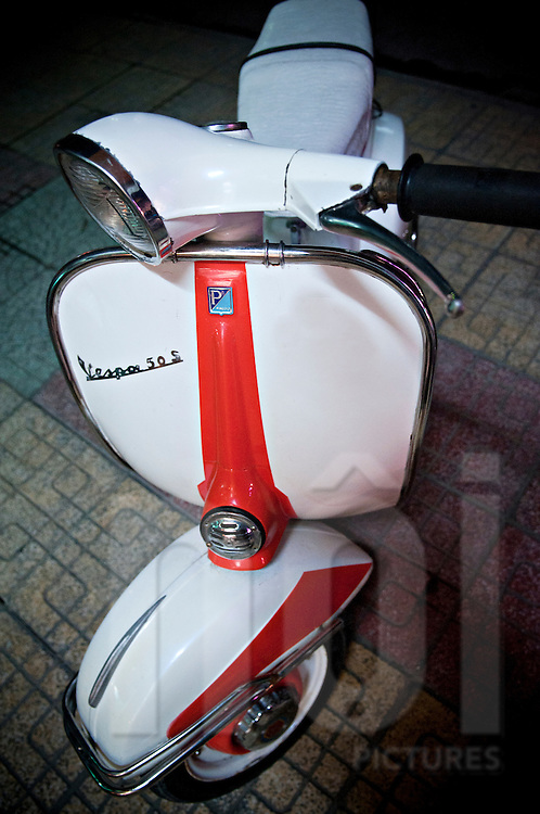 A vintage Vespa 50 S is parked in a street of Nha Trang, Vietnam, Asia. The motorbike is painted in white with a red strips