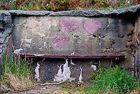 Lilla hjerter malt på en betongvegg over en benk på Tueneset.