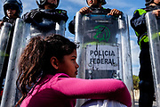 Honduran child migrant sits in front of the riot police officer at El Chaparral border crossing near the US-Mexico border in Tijuana, Mexico on November 22nd, 2018. The officers blocked the road due to the protest by the part of Central American migrants to seek asylum in the US.