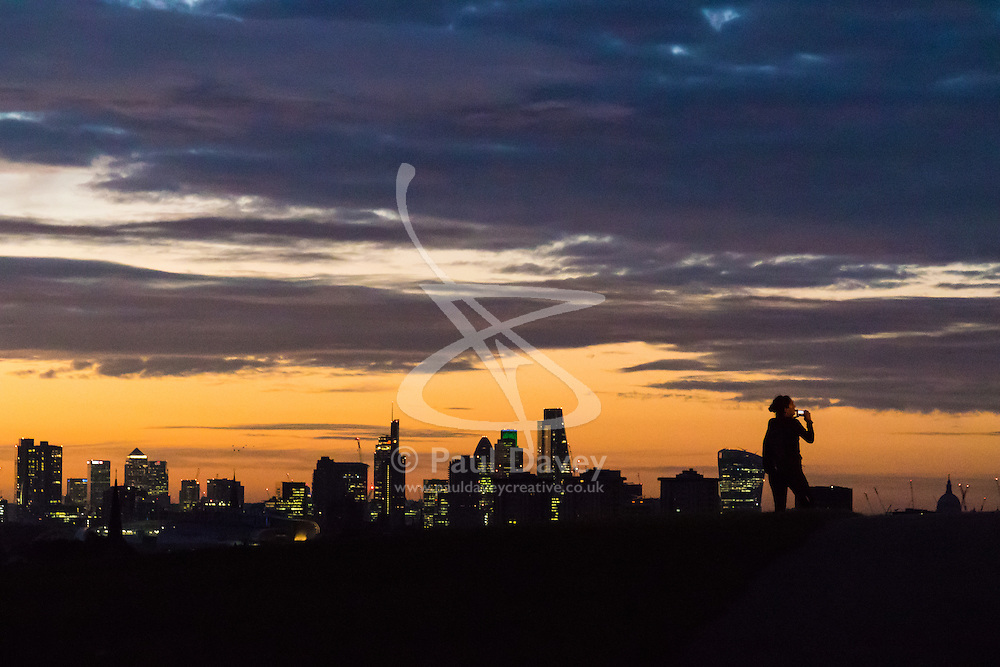 Primrose Hill, London, September 27th 2016. A woman photographs the pre-dawn skyline on Primrose Hill as a new day breaks over London. ©Paul Davey<br /> FOR LICENCING CONTACT: Paul Davey +44 (0) 7966 016 296 paul@pauldaveycreative.co.uk
