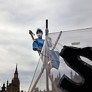 An anti-cut activist dressed up as a health worker sits on the top of one of the tri-pods used to block the bridge..The Health and Care Bill has been passed by Parliament and is due to go to the House of Lords. In protest against the bill which aim to deconstruct and privatise large parts of the NHS UK Uncut activists together with health workers and trade unionists blocked the Westminster Bridge from 1pm til 5.30pm.