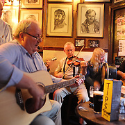 Musician's playing in O'Donoghue's Bar, Dublin, Ireland..O'Donoghue's is known for it's traditional Irish music. It has been frequented of the years by many musicians from the Dubliner's to Bruce Springsteen. O'Donoghue's is recognized as one of Dublin's most famous pubs and is frequented by locals and tourist alike to play a tune or enjoy a pint of Guinness. Dublin, Ireland. Photo Tim Clayton