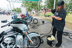 Leon Jube of North Dakota washes his Harley-Davidson Ultra Classic at the free Harley-Davidson bike wash at the annual Sturgis Black Hills Motorcycle Rally. SD, USA. August 6, 2014.  Photography ©2014 Michael Lichter.
