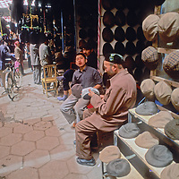 Hat merchants sit by their stalls in a covered bazaar in Kashgar (Kashi), a city on the ancient Silk Road in Xinjiang, China.