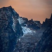 The first rays of light from sunrise bathe Grand Teton in orange light in late autumn near Jackson, Wyoming.