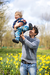 © Licensed to London News Pictures . 24/03/2021. Manchester , UK . Father DUNCAN STRUTHERS (36 from Chorlton) and his daughter AMELIE STRUTHERS (20 months) play amongst daffodils in the sunshine in Chorlton Park on the first week of Spring 2021 . Photo credit : Joel Goodman/LNP