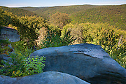 Rock outcroppings provide a vantage point to take in a sweeping view of the Minister Valley in the Allegheny National Forest in Warren County, Pennsylvania. The Allegheny Front was once part of a vast delta and layers of a hard, sandstone congolomerate were deposited. Between 250 and 320 million years ago, the Allegheny Front was lifted, forming hills and mountains. Over time, erosion exposed, split, or dislodged and moved the former sedimentary rock, resulting in large rock outcroppings.