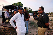 Naveed Ahmed, 27, (left) a young and ambitious member of the AVCC (Anti-Violence Crime Cell) is portrayed while waiting to leave for a night raid on the outskirts of Karachi, Pakistan's main economic hub, in Sindh Province. The AVCC is a special police unit mostly involved in anti-terrorism operations and kidnap cases in the city and its vicinity.