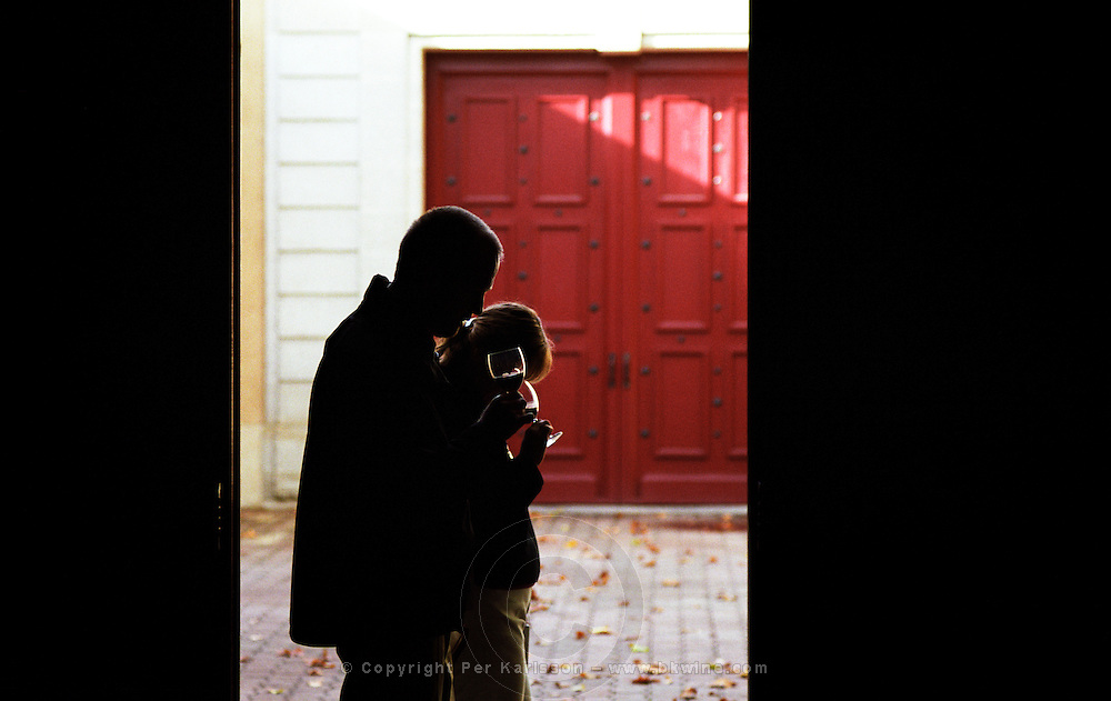 Dark Silhouettes of a man and a woman tasting wines glasses in hand in a doorway against a background of a red door, at Chateau Carbonnieux, Graves, Pessac-Leognan, Bordeaux Gironde Aquitaine France Europe