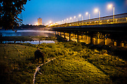 25th May 2014, Yamuna River, New Delhi, India. An elephant ridden by a handler walks on the Yamuna Bank near a bridge at dusk in New Delhi, India on the 25th May 2014<br /> <br /> Elephant handlers (Mahouts) eke out a living in makeshift camps on the banks of the Yamuna River in New Delhi. They survive on a small retainer paid by the elephant owners and by giving rides to passers by. The owners keep all the money from hiring the animals out for religious festivals, events and weddings, they also are involved in the illegal trade of captive elephants. The living conditions and treatment of elephants kept in cities in North India is extremely harsh, the handlers use the banned 'ankush' or bullhook to control the animals through daily beatings, the animals have no proper shelters are forced to walk on burning hot tarmac and stand for hours with their feet chained together. <br /> <br /> PHOTOGRAPH BY AND COPYRIGHT OF SIMON DE TREY-WHITE<br /> + 91 98103 99809<br /> email: simon@simondetreywhite.com photographer in delhi