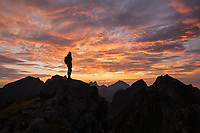 Silhouette of female hiker with colorful summer sunset behind the rugged mountain peaks of Moskenesøy, Lofoten Islands, Norway