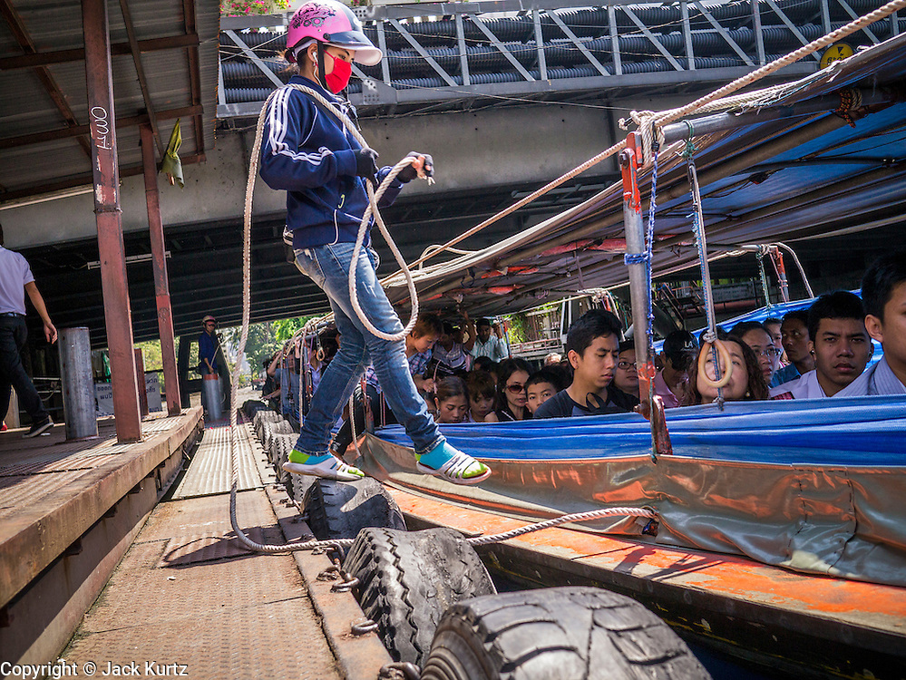 10 OCTOBER 2012 - BANGKOK, THAILAND:  An attendant gets back on a fast passenger boat on Khlong Saen Saeb at the AsokPetchaburi Pier in Bangkok. Bangkok used to be criss crossed by canals (called Khlongs in Thai) but most have been filled in and paved over. Khlong Saen Saeb is one of the few remaining khlongs in Bangkok with regular passenger boat service. Boats and ships play an important in daily life in Bangkok. Thousands of people commute to work daily on the Chao Phraya Express Boats and fast boats that ply Khlong Saen Saeb. Boats are used to haul commodities through the city to deep water ports for export.     PHOTO BY JACK KURTZ