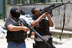 Policiais fazem guarda durante a incursão na favela do Morro do Alemão em 28 de novembro de 2010 no Rio de Janeiro, Brasil. Após dias de preparação, forças de segurança do Brasil, lançaram um ataque contra uma favela, onde entre 500 e 600 traficantes de drogas estão escondidos e recusam a se render. Cerca de 2.600 tropas aerotransportadas, marines e membros das unidades de elite da polícia participaram da operação como alvo um grupo de favelas sem lei conhecido como Complexo de Alemão. FOTO: Jefferson Bernardes/Preview.com